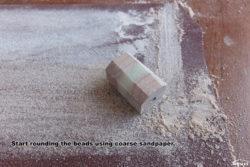 Start rounding the beads using coarse sandpaper.